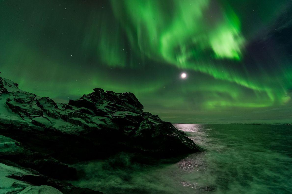 A lua brilha através de uma aurora boreal em Laksefjorden, na Noruega.