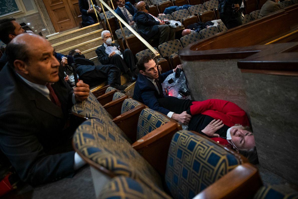 Jason Crow, representante do Colorado, conforta a representante da Pensilvânia, Susan Wild, enquanto os insurgentes interrompiam ...
