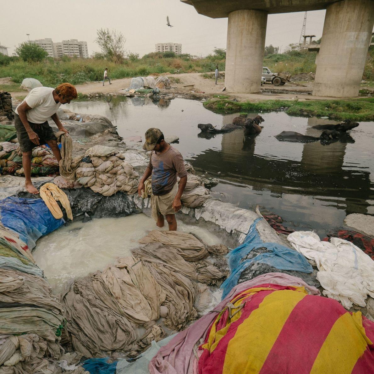 Fotografia de homens a branquearem a roupa suja antes de a atirarem para o Rio Yamuna