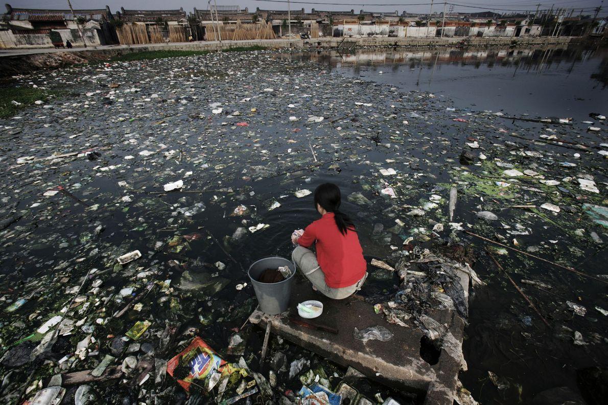 Uma mulher sentada num dos rios e lagos gravemente poluídos, na província de Cantão.