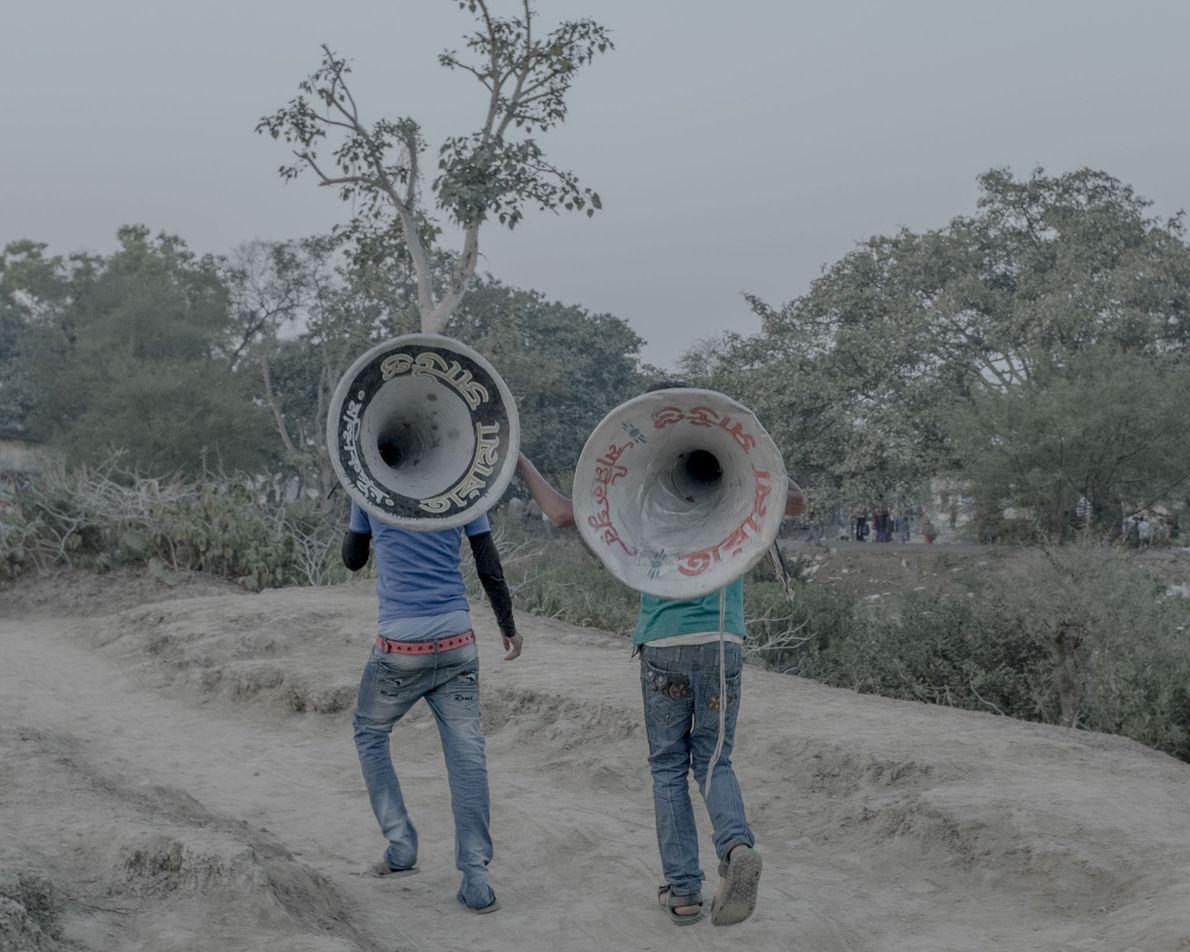Dois jovens carregam altifalantes.