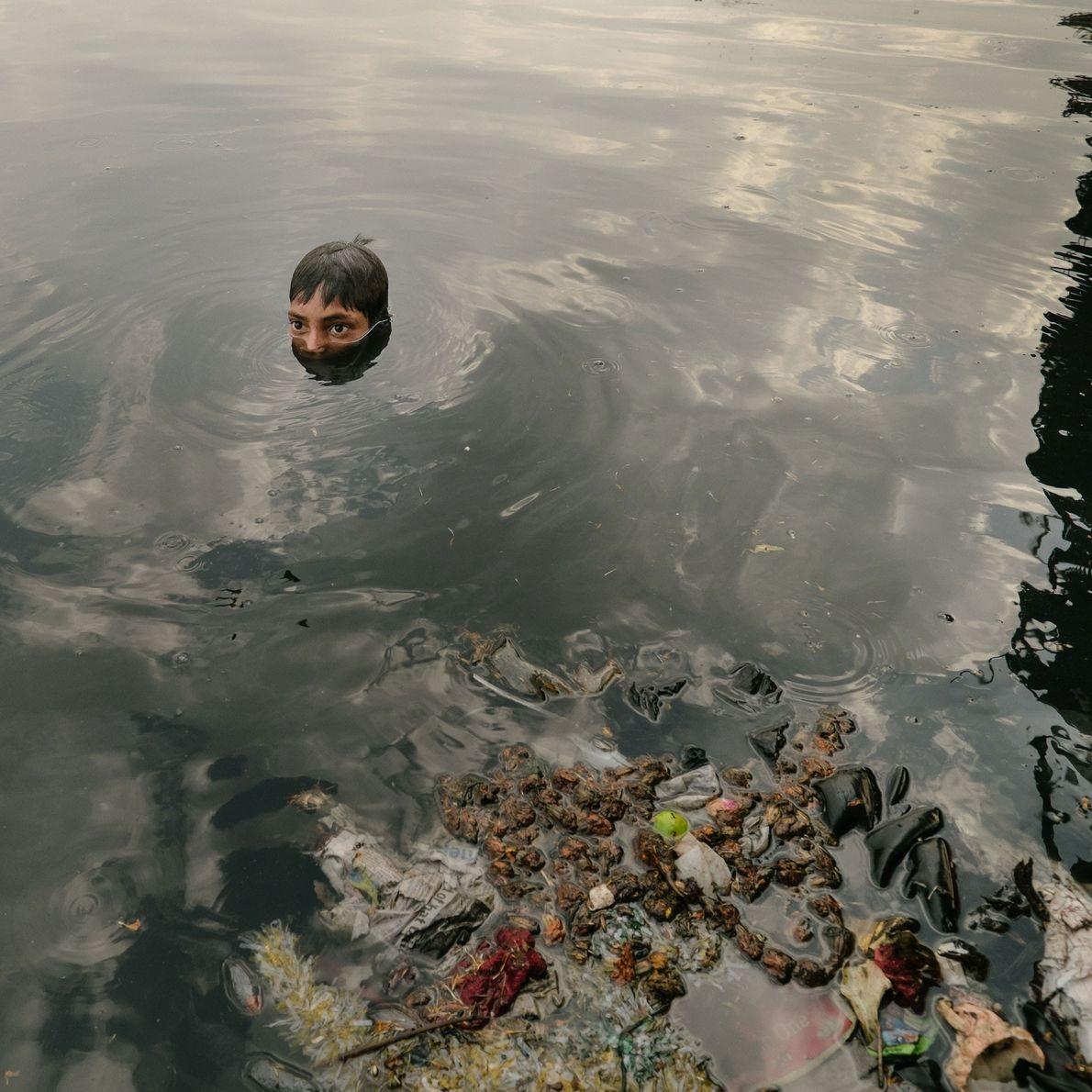 Crianças, que vivem debaixo da antiga Ponte de Ferro, vasculham o lixo.