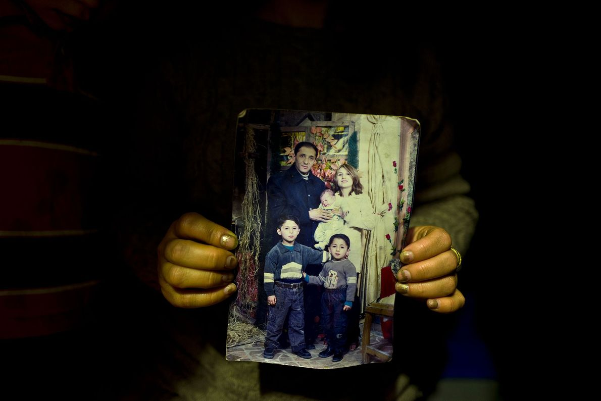 Fidan Kiru segura uma fotografia sua, do seu marido e dos três filhos.