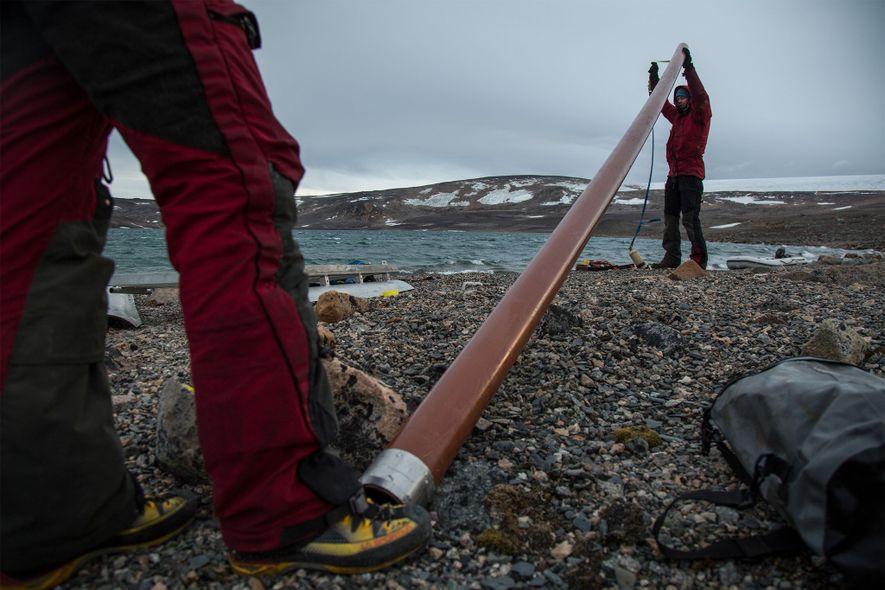 A equipa de cientistas prepara um tubo para recolher amostras de sedimentos do lago na costa ...