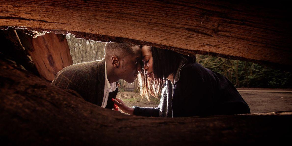 Casal em momento privado junto a uma árvore