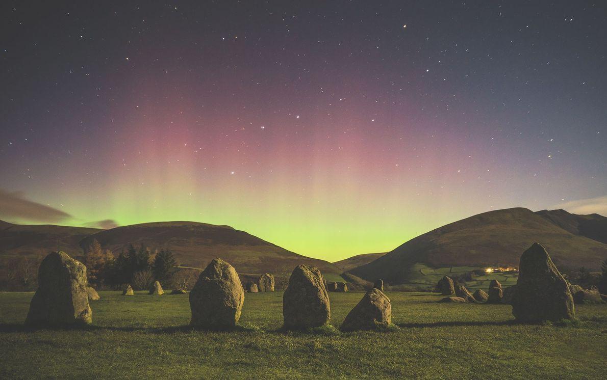 A aurora boreal ilumina os montes que circundam o círculo de pedra de Castlerigg em Cumbria, ...