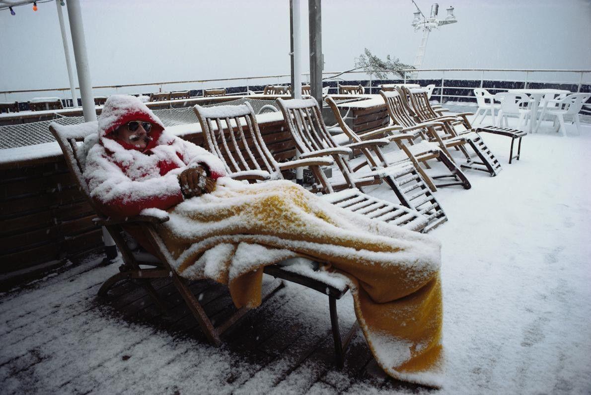 Um turista determinado dorme numa espreguiçadeira durante uma nevada.