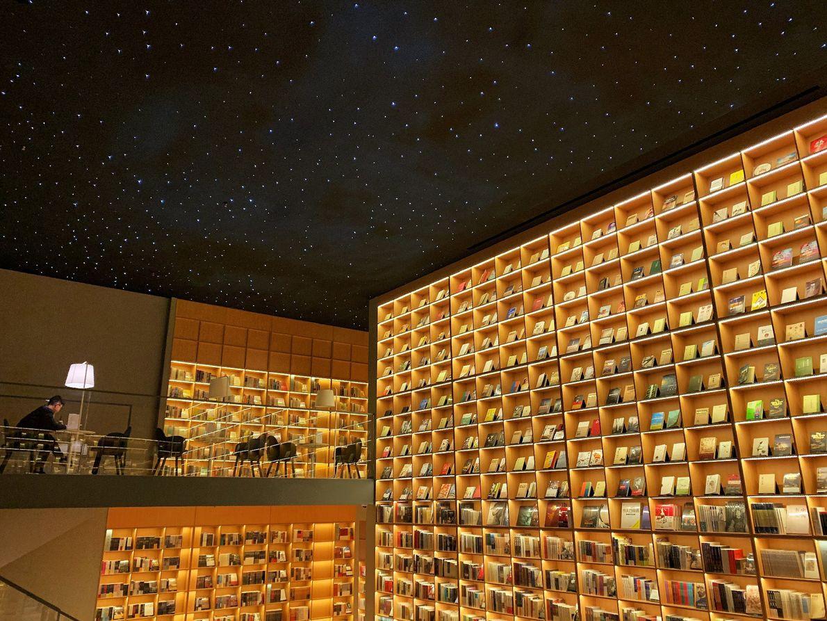 Um homem a ler sob o teto estrelado no Light Space, uma livraria em Changzhou, na ...