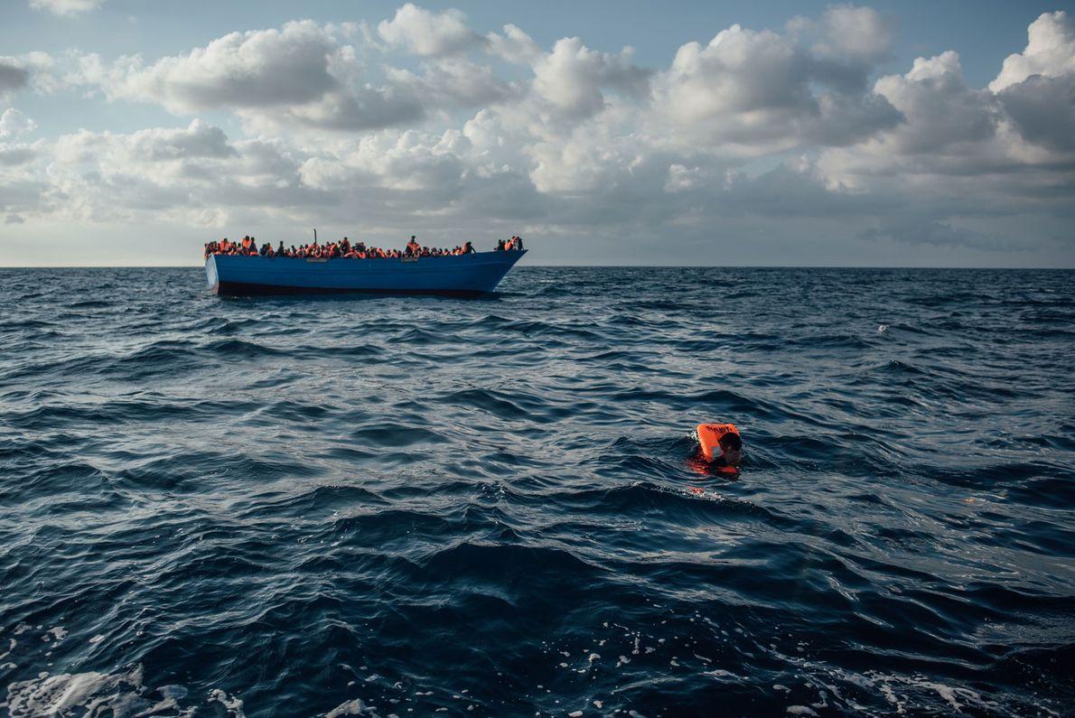 Elementos da equipa de resgate, a bordo de um semi-rígido insuflável, entregam coletes salva-vidas aos refugiados.