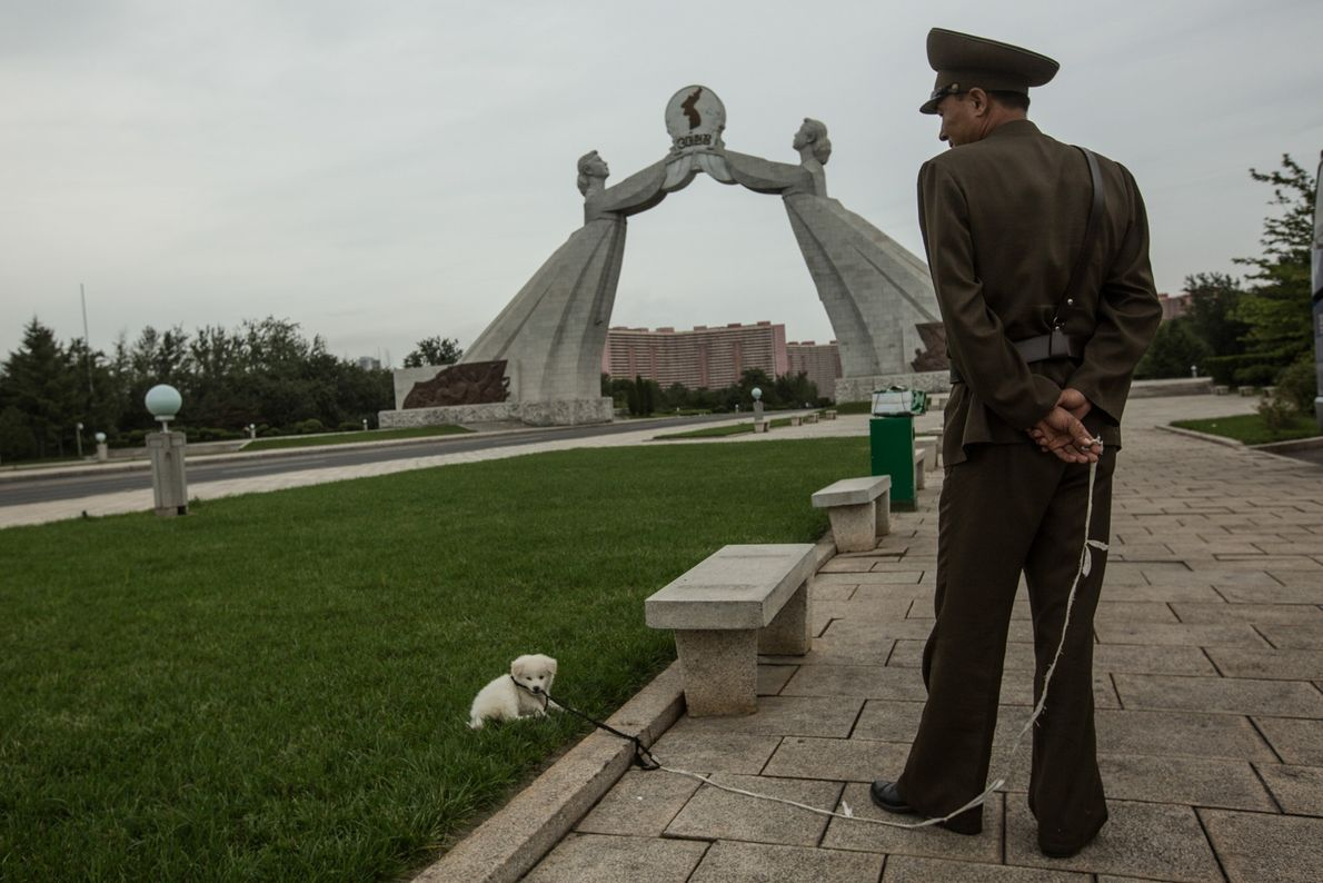 Um soldado e um cão de estimação perto de uma estátua