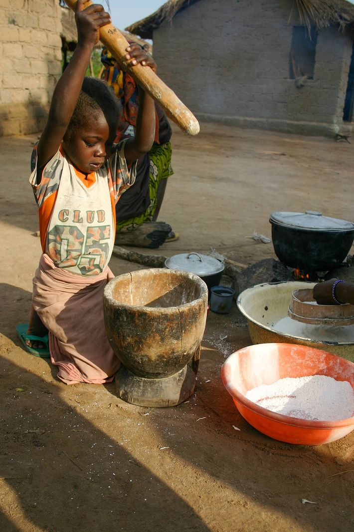 Uma criança bate mandioca — um importante marco na África subsariana. A fotografia foi tirada em ...
