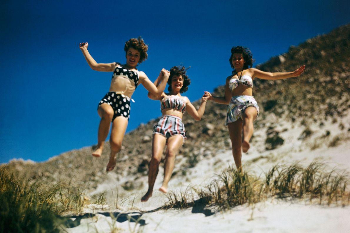 Três jovens mulheres em biquíni divertem-se.