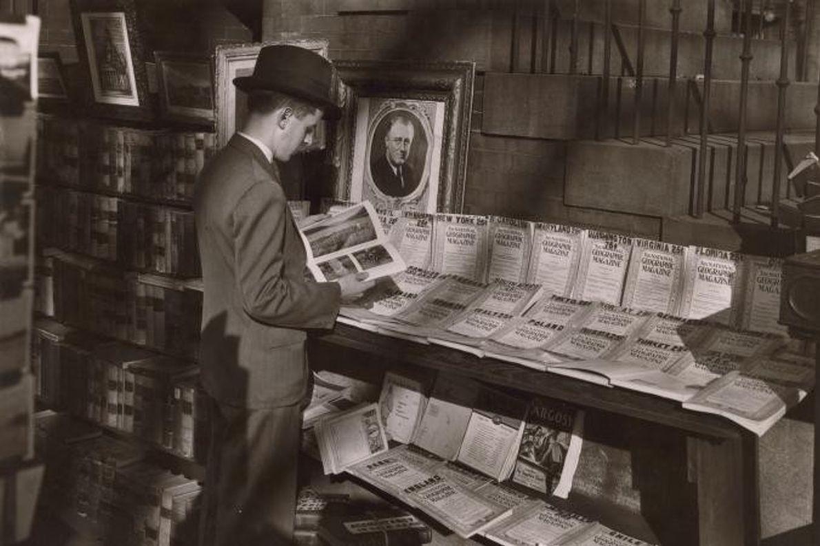 Um homem folheia uma revista junto a uma banca de jornais em Pennsylvania Avenue, no estado ...