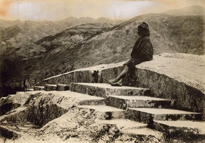 No Peru, um habitante local está sentado no topo da fortaleza Inca Saqsayhuamán, com vista para ...