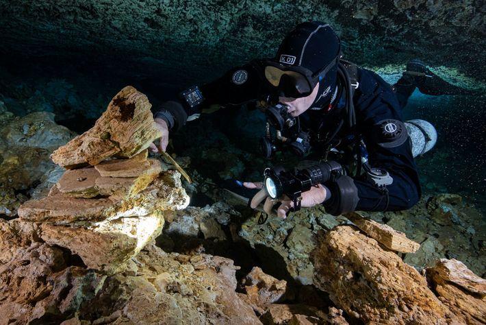 Um mergulhador examina as pedras empilhadas por antigos mineiros que há 10 ou 12 mil anos ...