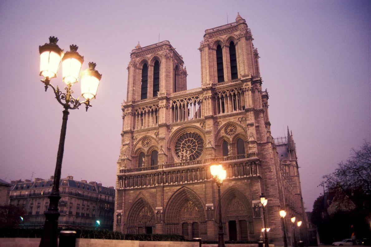 Candeeiros de rua iluminam Notre-Dame durante o crepúsculo.