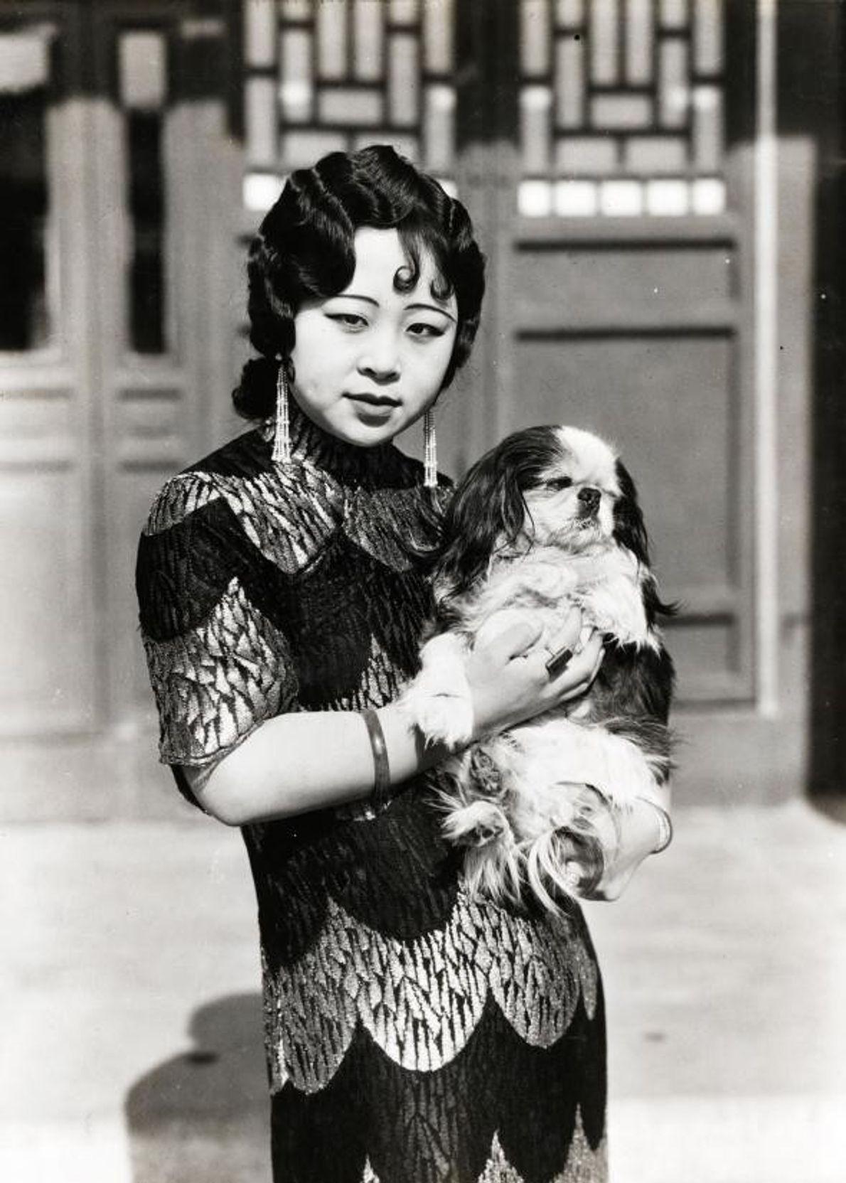 Uma elegante princesa manchu, casada com um príncipe mongol, segura o seu cão ao colo em ...