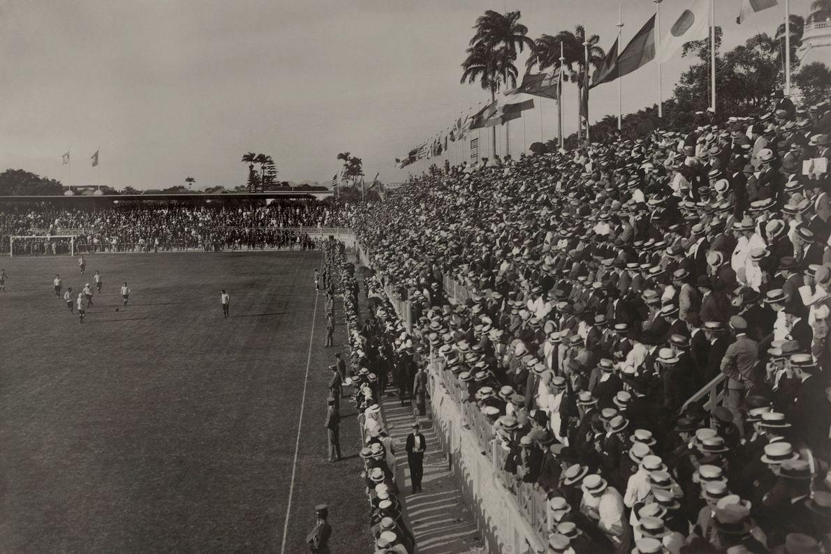 Uma multidão assiste a uma partida de futebol.