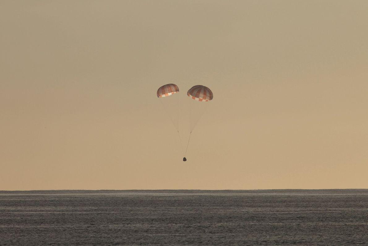 Uma nave Dragon a cair de paraquedas no Oceano Pacífico, depois de completar a sua rota ...