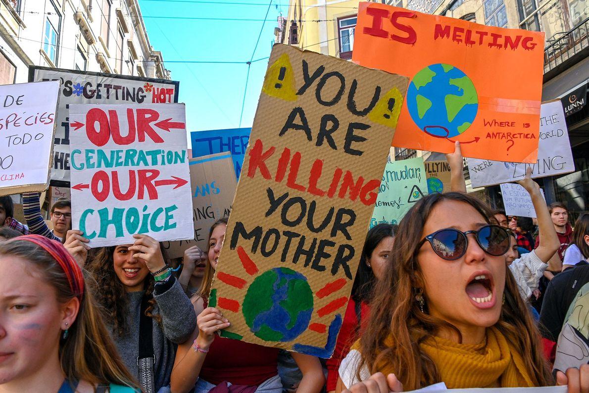 Estudantes portugueses cantam e exibem cartazes, em frente ao parlamento.