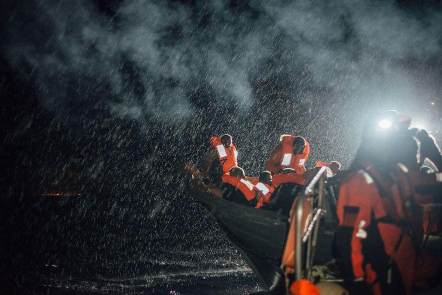 Sob uma chuva miudinha, os refugiados aguardam pela sua vez de subir a bordo do semi-rígido ...