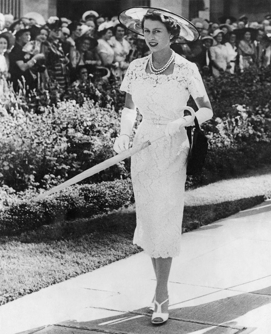 Enfeitada com um chapéu branco de palha e um vestido de renda, Sua Majestade exibe-se numa ...