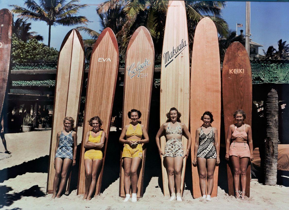 Um grupo de mulheres posa em frente de pranchas de surf em Waikiki Beach, em Honolulu, ...