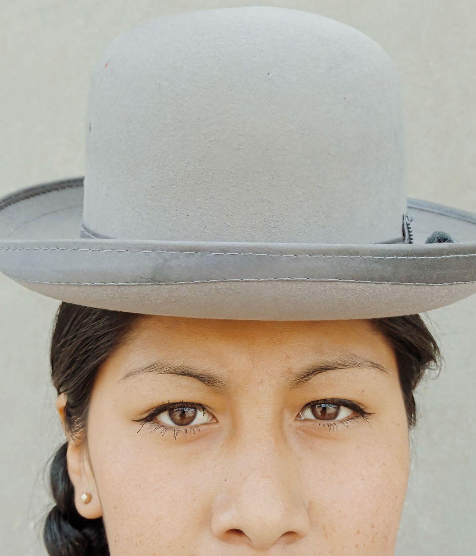 Wara olha diretamente para a objetiva, com o seu chapéu de coco.