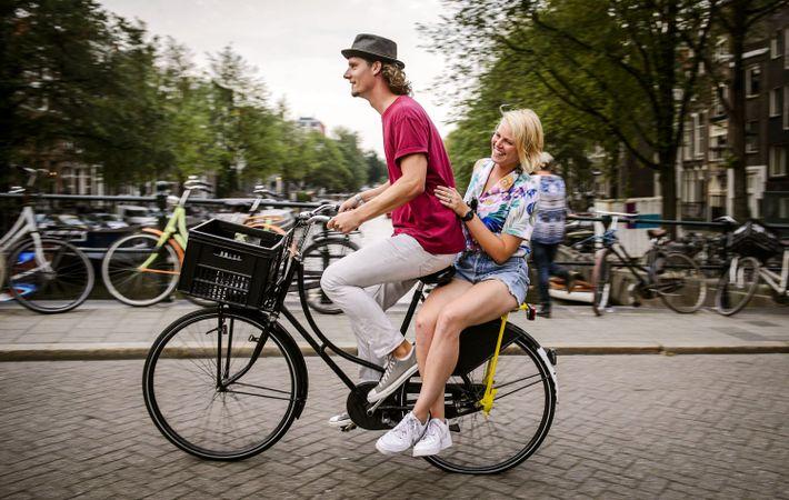 Imagem de duas pessoas a andar de bicicleta em Amesterdão.