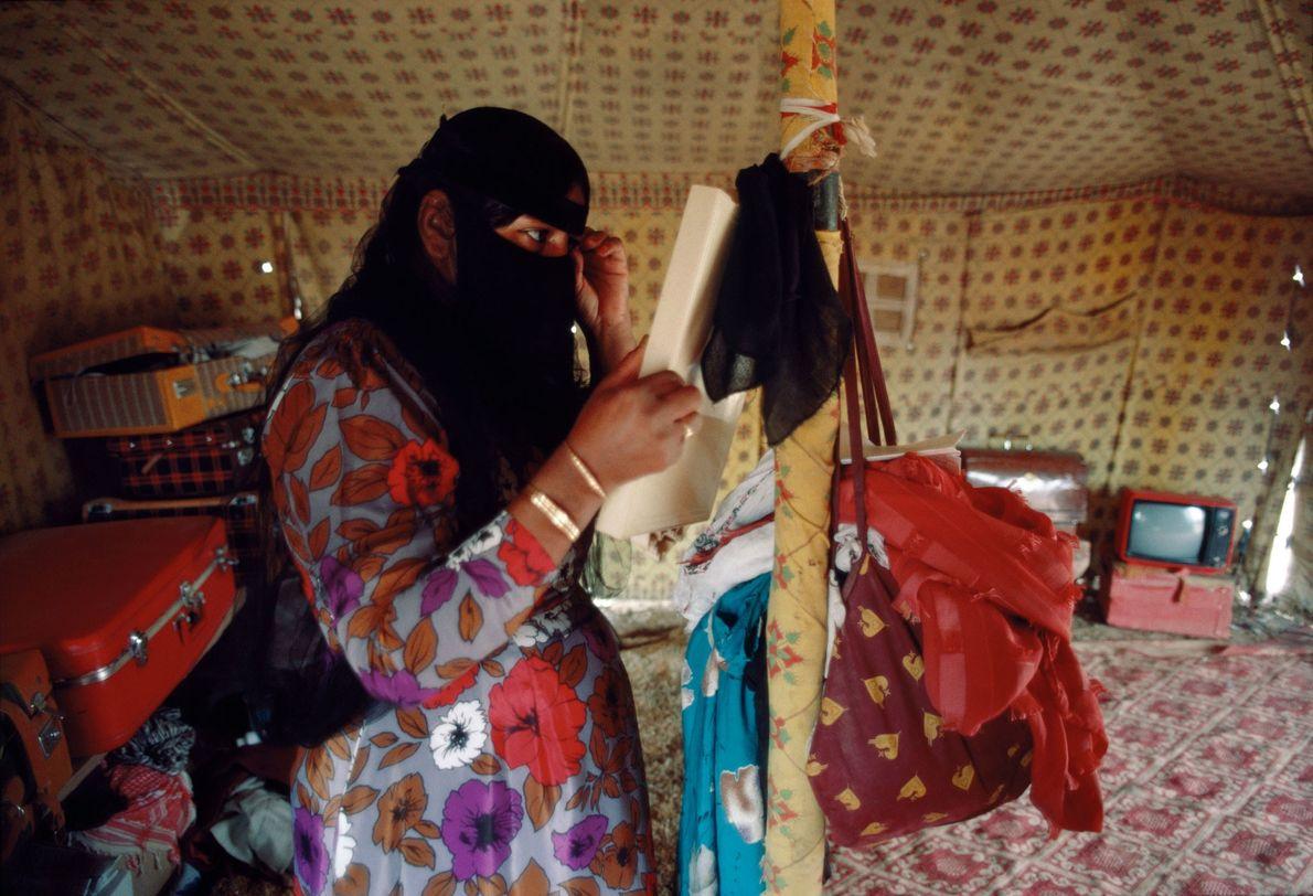 Uma mulher beduína ajusta o véu, numa tenda em Wadi Nisah, na Arábia Saudita.