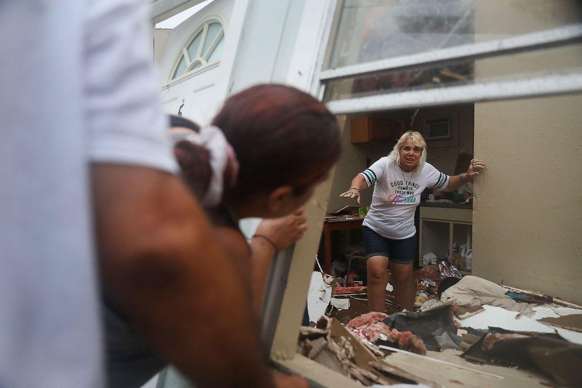Uma mulher abre caminho por entre os destroços