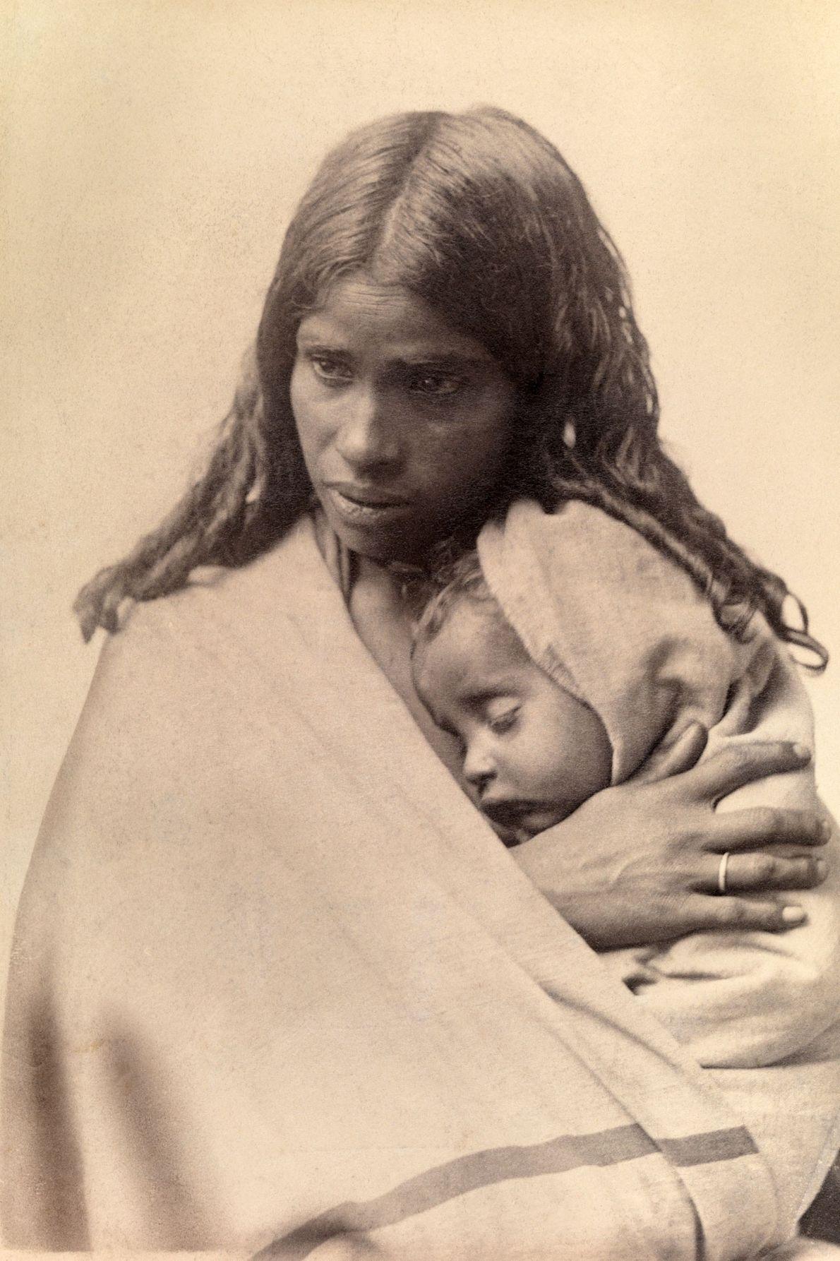 Uma criança da tribo Toda dorme sobre o peito da sua mãe.