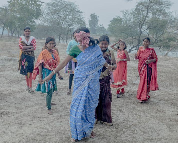 Um grupo de mulheres joga à apanhada.