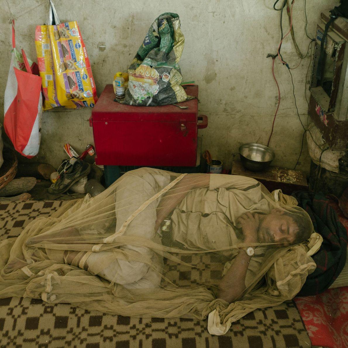 Fotografia de um homem a dormir dentro de um mosquiteiro