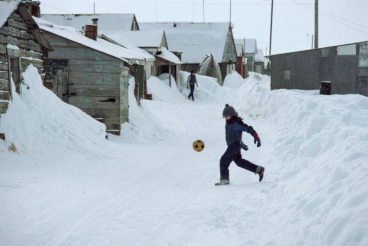 Um rapaz pontapeia uma bola de futebol numa rua coberta de neve.