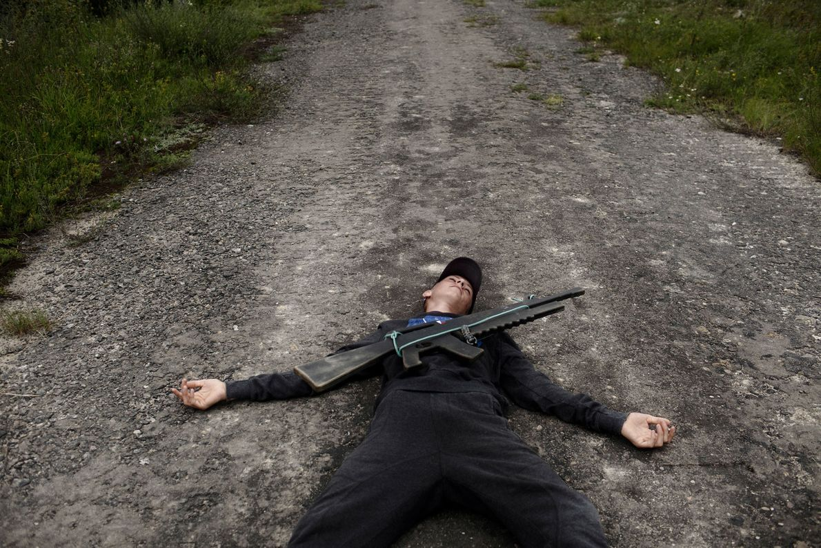 """Um jovem ucraniano, deitado no chão, fingindo ter sido atingido por """"fogo inimigo"""", durante um exercício ..."""