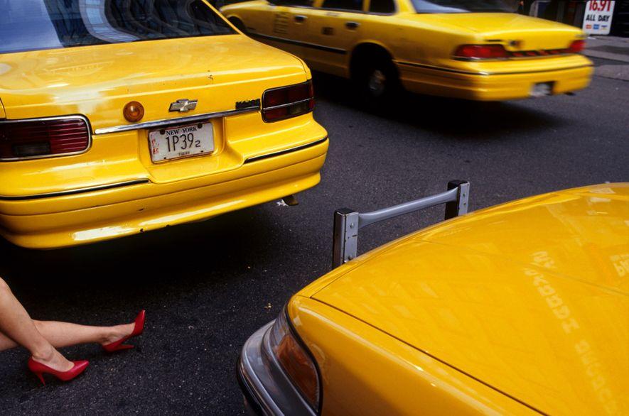As pernas de uma mulher, com saltos altos vermelhos, no meio de táxis em Times Square.