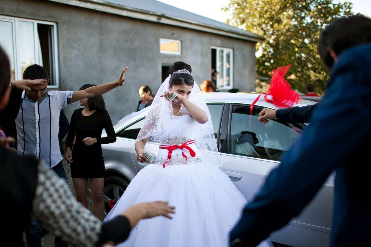 Imagem de uma noiva a chorar enquanto familiares dançam à sua volta