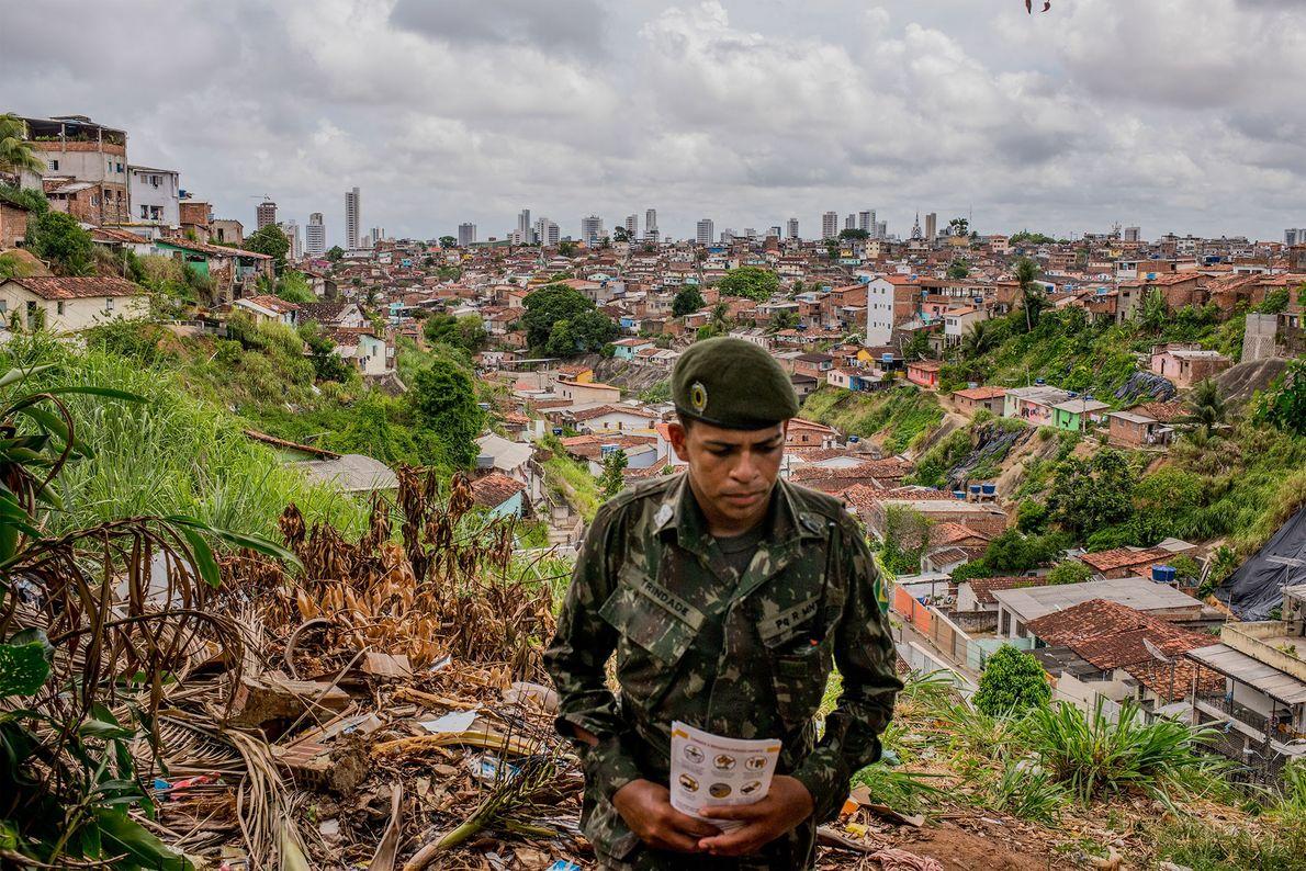 Um soldado a distribuir folhetos numa favela