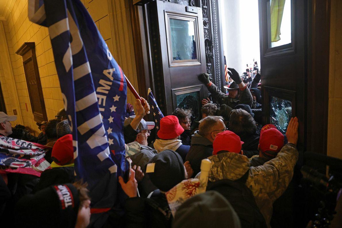 Uma multidão com bandeiras e estandartes de Trump invadiu as portas do Capitólio dos EUA, quebrando ...