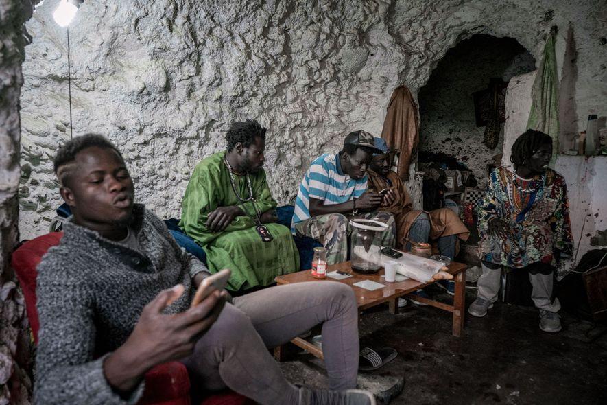 Imigrantes senegaleses convivem sentados no interior de uma gruta na parte superior da montanha. Embora as ...