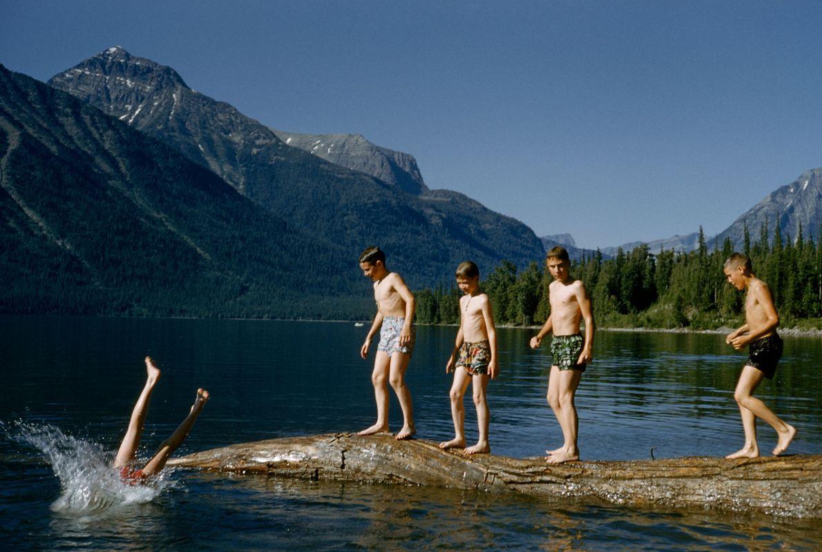 Rapazes à espera de vez para mergulharem de um tronco, no lago McDonald, no Parque Glaciar ...