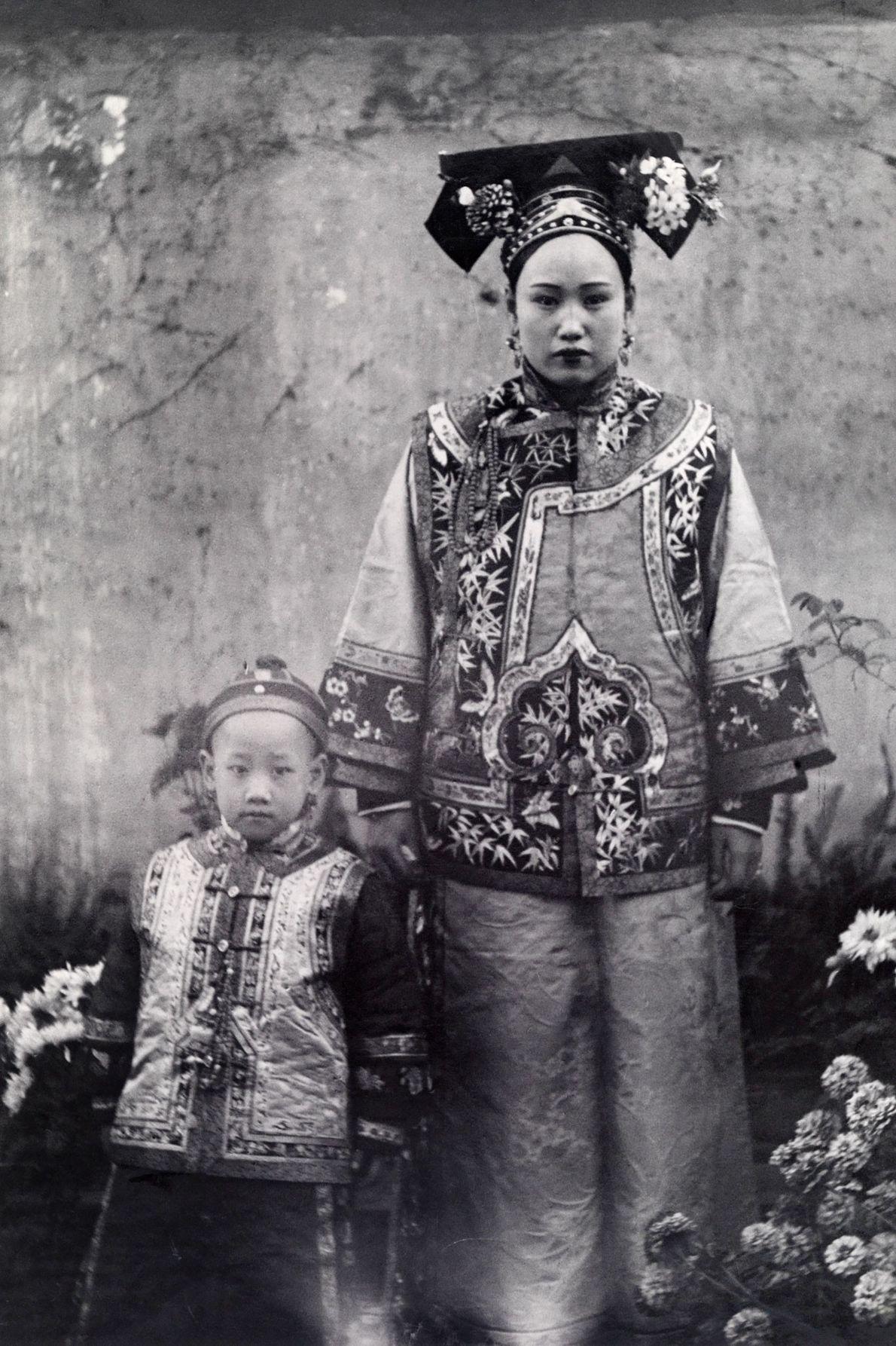 Uma mãe chinesa e a filha envergam o traje tradicional da região manchu.