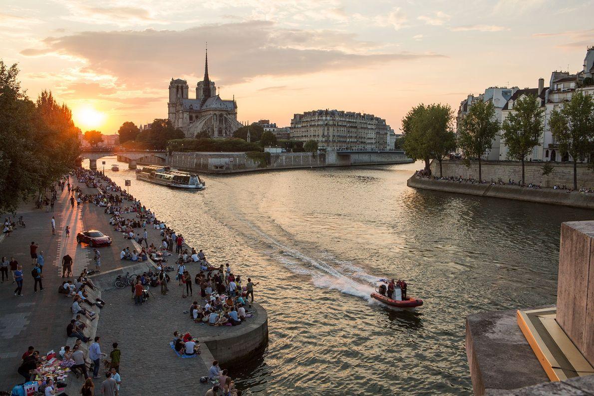 As margens do Rio Sena cheias de parisienses ao pôr-do-sol.