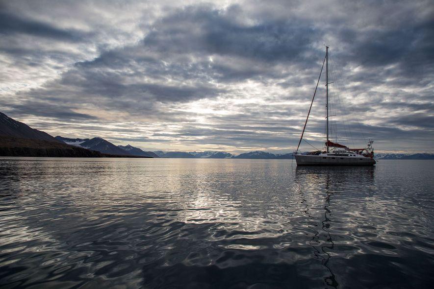 O veleiro ancorado num dia calmo ao largo do arquipélago de Svalbard.