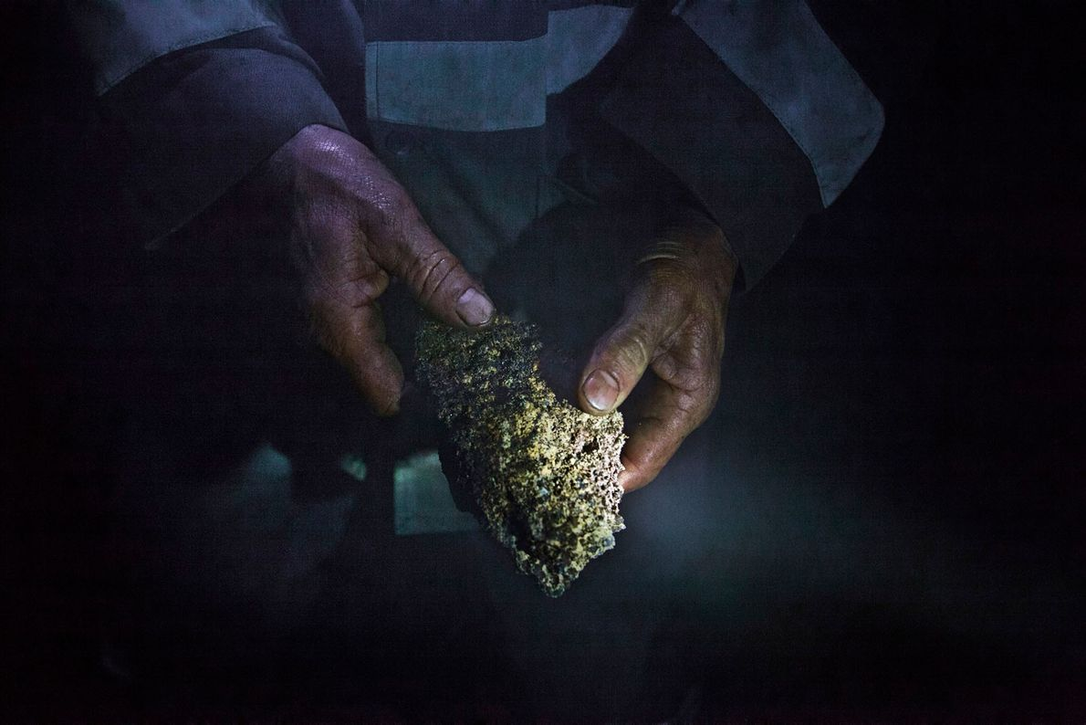 Mineiro mostra um pedaço de manganês coberto de terra