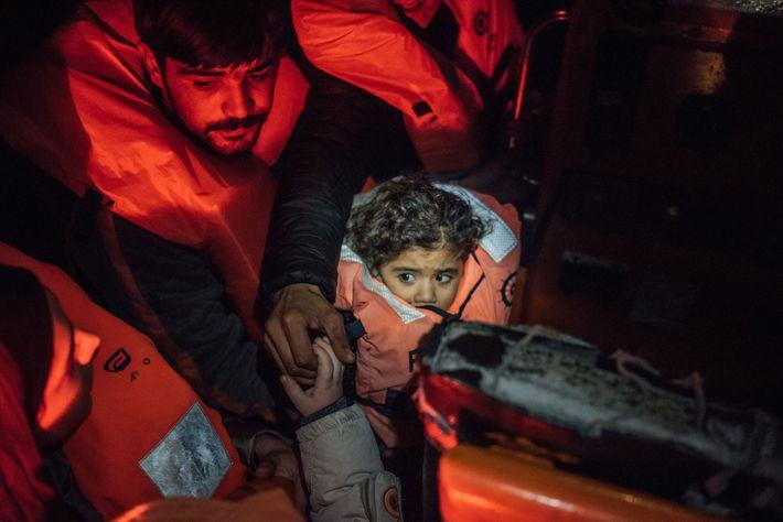 Uma criança síria segue apertada a bordo de uma embarcação de salvamento.