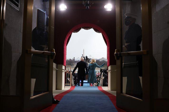 O casal Biden caminha sobre um tapete azul e vermelho em direção ao palco na ala ...