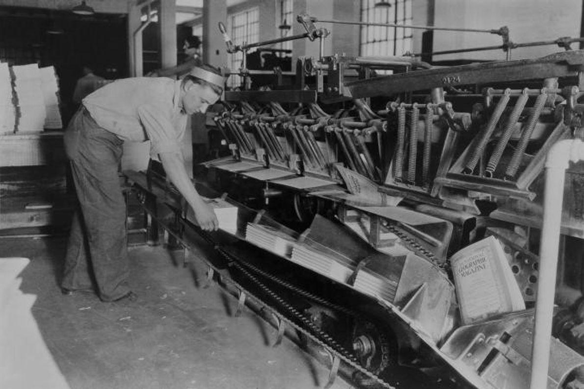 Uma máquina de grampar e de impressão de capa produz várias cópias de uma revista.