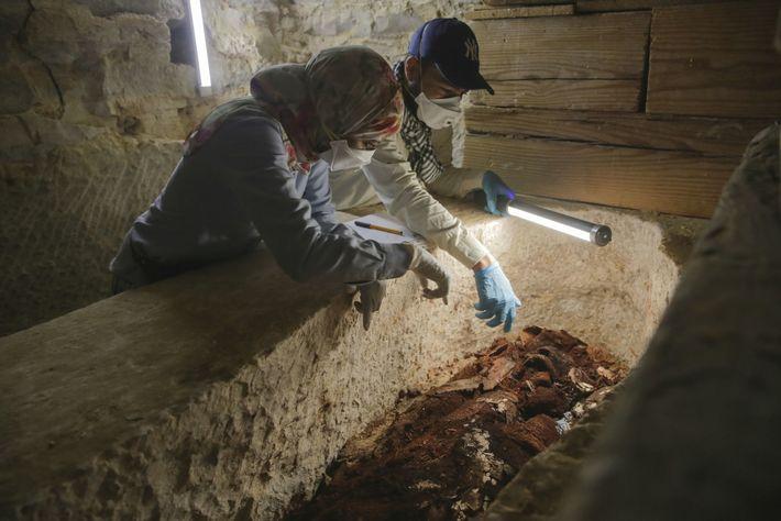 Os arqueólogos Maysa Rabeeh (à esquerda) e Mohammed Refaat (à direita) examinam um caixão de madeira ...